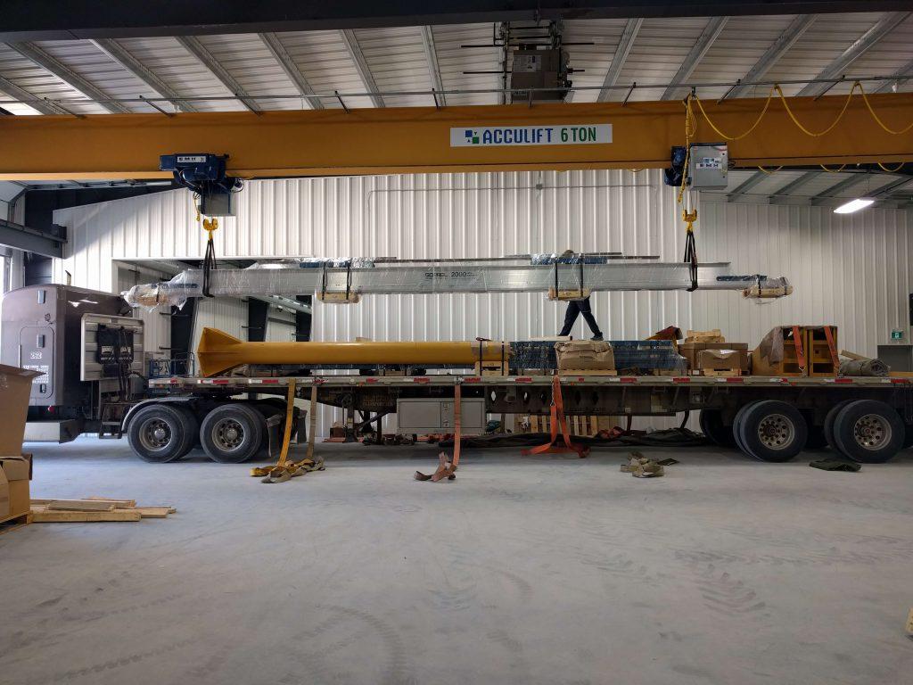 top running bridge crane being handled by underhung overhead crane.