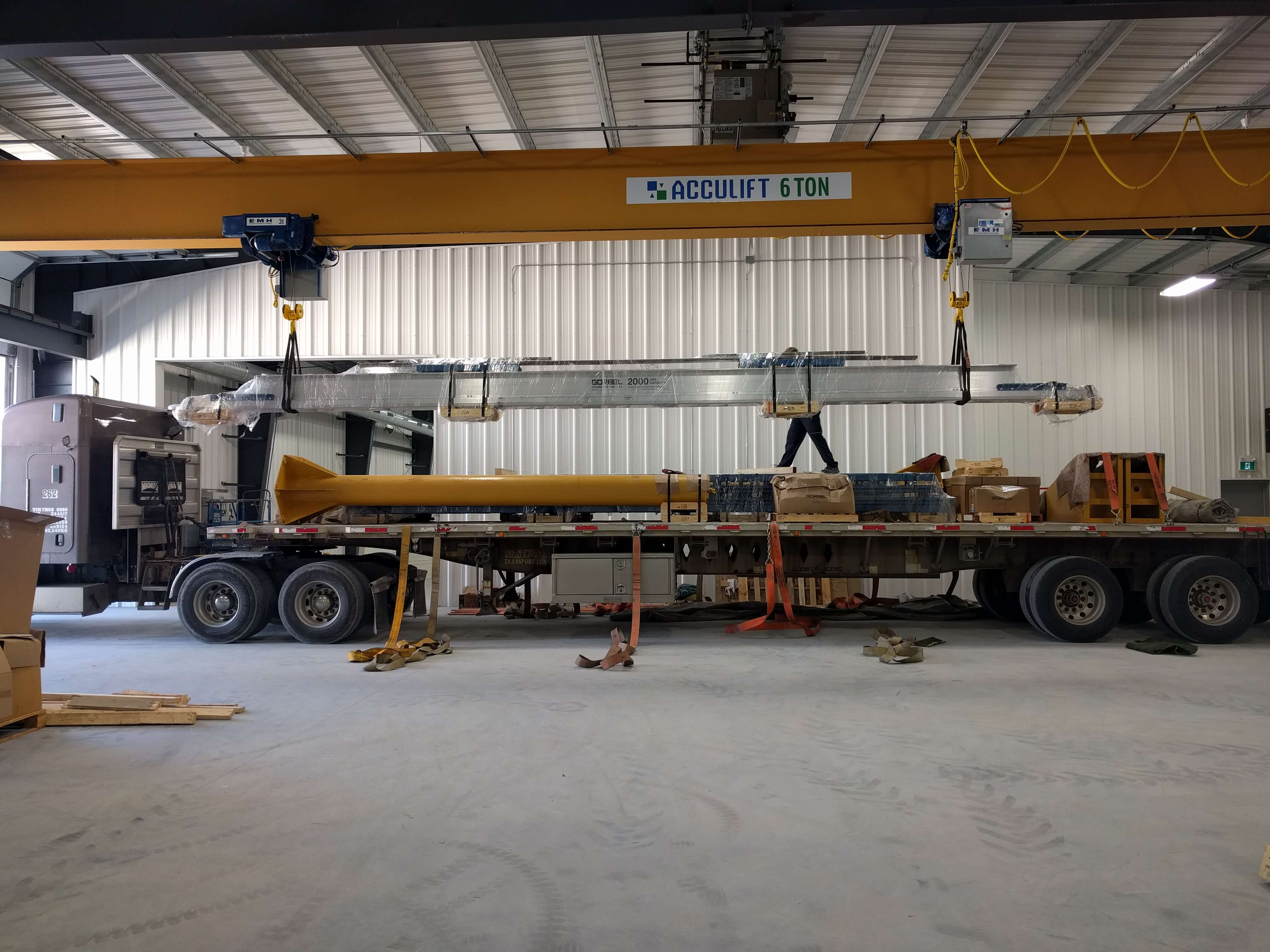 top running bridge crane being delivered and handled by overhead crane.