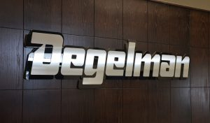 degelman logo behind their office desk