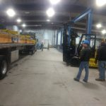 supervisor watching forklift moving crane parts off of truck