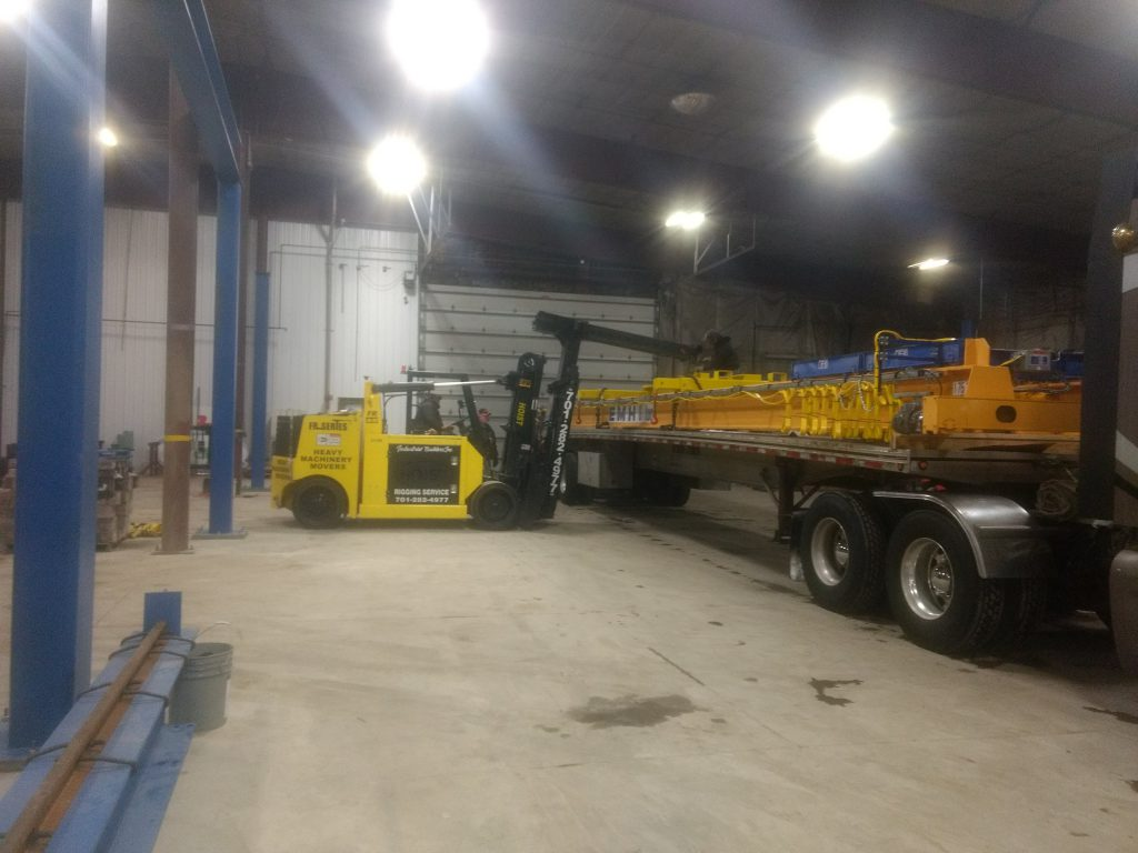 forklift moving crane parts off of truck