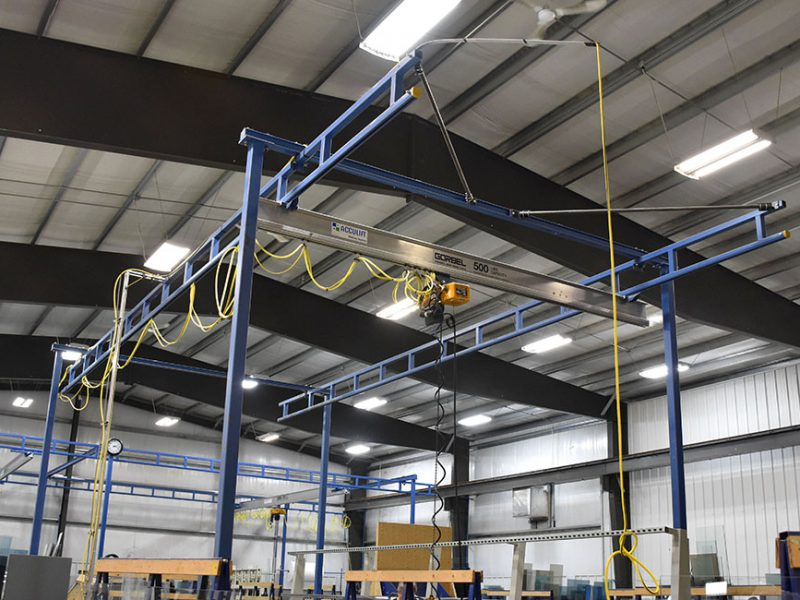 High workstation lift crane solution from acculift extra supports on cantilevered header.